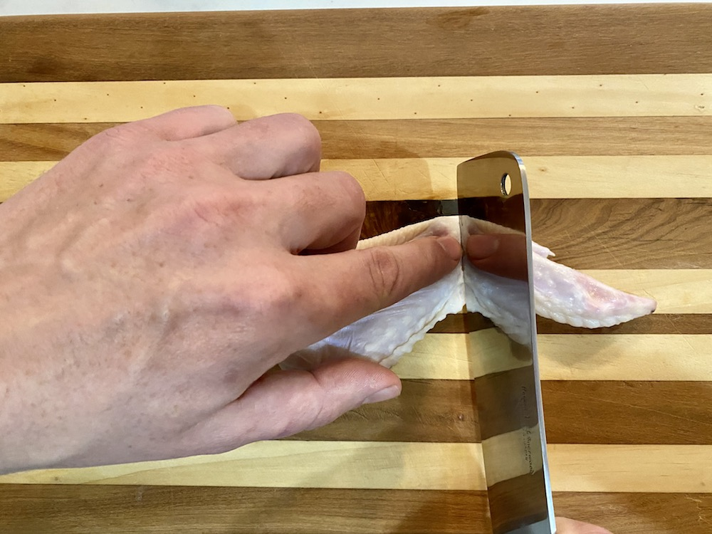 Cutting a raw chicken wing.