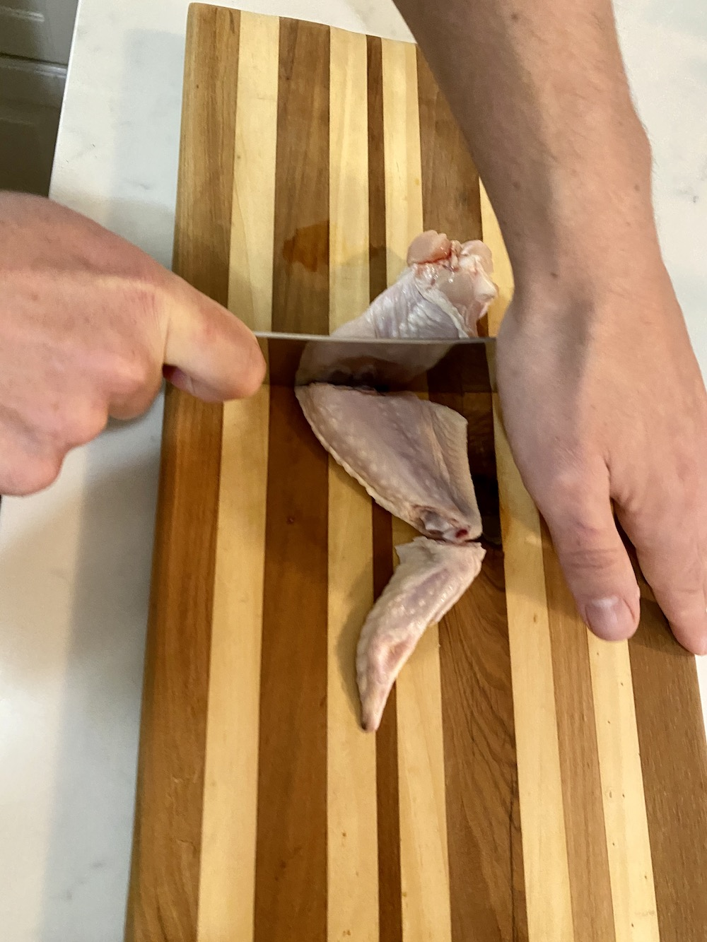 Cutting a chicken wing.